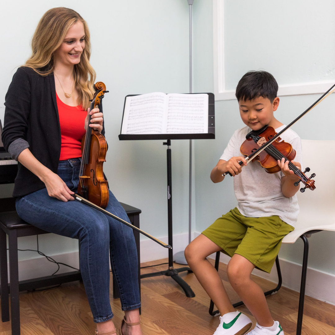 teacher and child playing violin