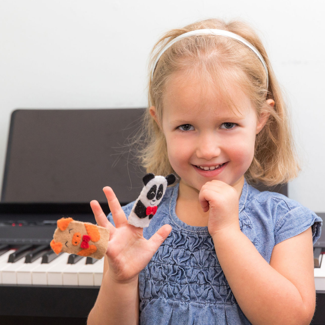 girl smiling in front of a piano