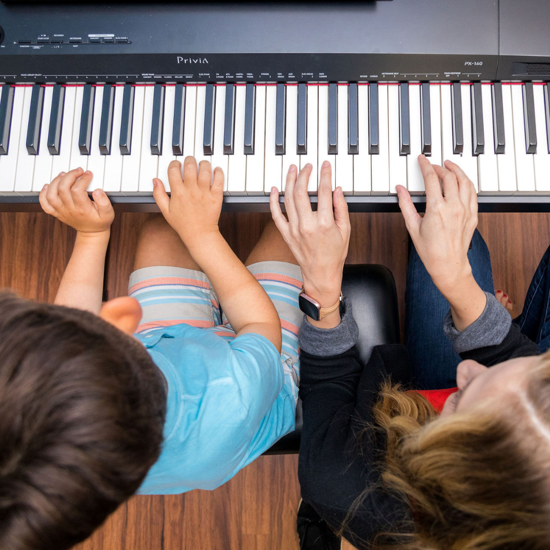 child and adult playing piano